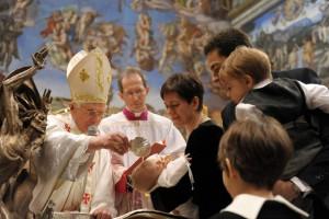 Pope Emeritus Benedict XVI baptizing a baby.